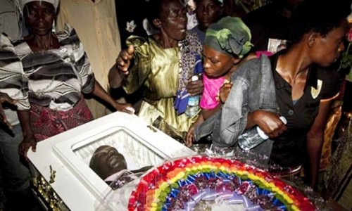 David Kato in his coffin on the day of his funeral, surrounded by his family.jpg